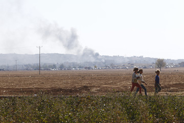 Girls walk in a field as smoke rises over the Syrian town of Kobani in the background, in Caykara