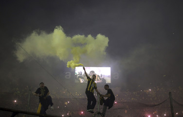 Fans of Penarol release yellow smoke as they cheer for their team before the Copa Libertadores first leg final soccer match against Santos in Montevideo