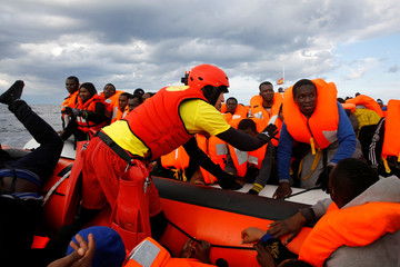 Migrants try to reach a rescue craft from their overcrowded raft, as lifeguards from the Spanish NGO Proactiva Open Arms rescue all on aboard, in the central Mediterranean Sea