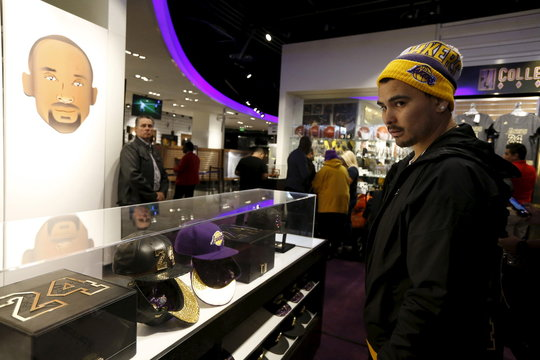 A fan looks at a Kobe Bryant 18k gold and leather baseball cap and a purple diamond cashmere baseball cap in the Lakers store at Staples Center on the last day of Kobe's 20-year career with the team, in Los Angeles