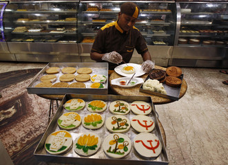 Kartik Chandra, a confectioner, makes symbols of different Indian political parties on sweets at a shop ahead of the general election in Kolkata