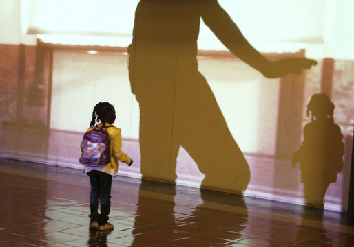 """Girl looks at shadow of performer from L.A. Dance Project during dress rehearsal for experimental opera """"Invisible Cities"""", which is presented inside the historic Los Angeles Union Station in California"""