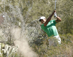 Tiger Woods of the U.S. hits his second shot from a waste area on the 10th hole during the first round of the WGC-Accenture Matchplay Championships golf tournament in Marana