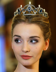 A debutant poses with her tiara designed by Karl Lagerfeld for the Opera Ball during a news conference in Vienna