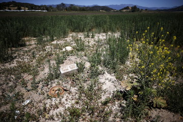 A cinder block and a piece of metal lie on the dry bed of a part of Lake Casitas that was formerly under water and stretched to the white RVs parked in the background, in Ojai