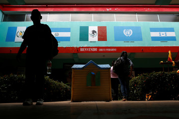 A man walks past pictures of Mexico's and other Central America countries' flags at Belen migrant shelter in Tapachula, Chiapas, Mexico