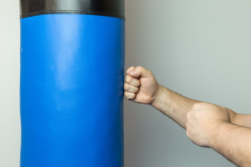 Fighter with bare hands punching straight on a blue punching bag