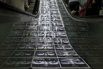 An artwork depicting photographs of occupy protesters and protest messages, made by a local artist is seen on an escalator, in Hong Kong's financial central district