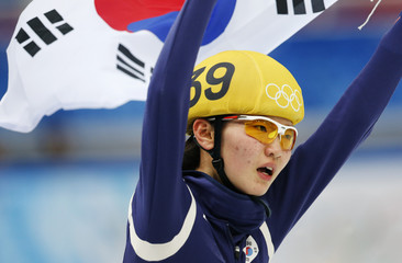 Shim Suk-hee of winner South Korea's skating team celebrates and holds up her national flag after the women's 3,000 metres short track speed skating relay final event in the Iceberg Skating Palace at the Sochi 2014 Winter Olympic Games