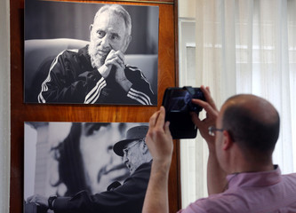 A man takes photos at  pictures of late Cuban leader Fidel Castro inside the Cuban Embassy in Buenos Aires, in Buenos Aires, Argentina