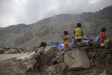 Nepalese children run next to their makeshift shelter near a landslide area after the April 25 earthquake at Jure village in Sindhupalchowk