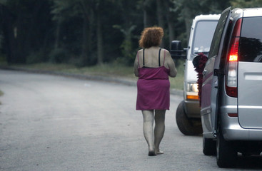 A prostitute waits for customers along a road of the Bois de Boulogne in Paris
