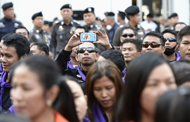 Riot police officer takes picture while standing guard as anti-government protesters break down barriers at Thai Police Headquarters in Bangkok