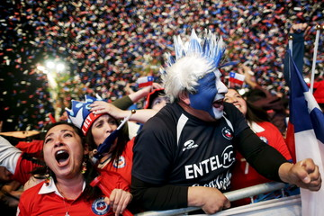 Fans of Chile celebrate their second goal against Peru while watching a broadcast of the Copa America semi-final soccer match at the Fan Fest in Santiago