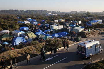 """A gendarme van patrols next to tents and makeshift shelters in the """"new jungle"""", a field where migrants and asylum seekers stay in Calais"""