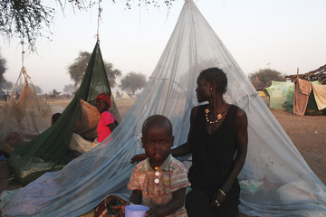 Two woman displaced by the fighting in Bor county look to each other as they sit by their mosquito nets in Minkaman, in Awerial county