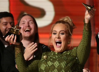 "Adele breaks the Grammy for Record of the Year for ""Hello"" after having it presented to her at the 59th Annual Grammy Awards in Los Angeles"