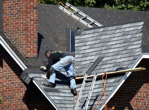Roofer adjusts shingles at job site in Washington
