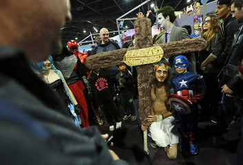 A participant dressed as Jesus Christ poses for a picture besides a young boy wearing a superhero Captain America costume during the first edition of HeroFestival in Marseille