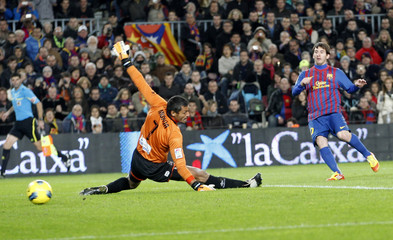 Barcelona's Lionel Messi scores against Levante UD goalkeeper Munua during their Spanish first division soccer match at the Nou Camp stadium in Barcelona