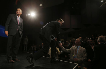 U.S. Republican presidential candidate and former Texas Governor Perry bends down to shake hands with an audience member as Ohio Governor Kasich looks on after the conclusion of the Voters First Presidential Forum in Manchester