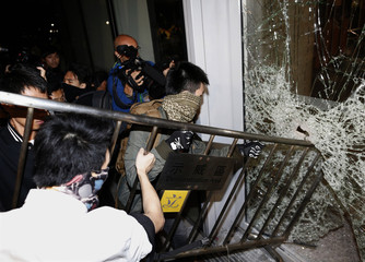 Masked pro-democracy protesters try to break  with a fence a glass window of the Legislative Council in Hong Kong