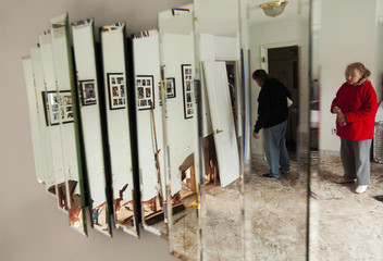 A woman and her husband survey flood damage to the inside of their home in the New Dorp Beach neighborhood of the Staten Island borough of New York