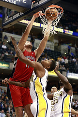 Toronto Raptors center Jonas Valanciunas of Lithuania dunks the ball challenged by Indiana Pacers forward Paul George and center Roy Hibbert during the first quarter of their NBA basketball game in Indianapolis