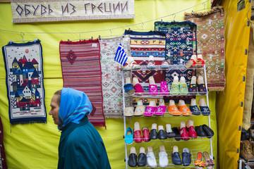 Woman walks past shoe stall at market in Black Sea resort town of Alushta