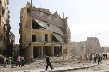 Residents inspect a site hit by what activists said was a barrel bomb in Aleppo's al-Ansari neighbourhood
