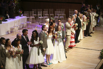 Couples look to the audience after being married in a mass ceremony on the stage of the Royal Festival Hall in London