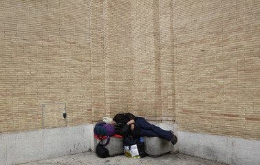 A homeless man sleeps in front of Saint Peter's Square in Rome