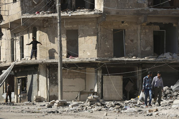 Residents walk past a damaged building in Aleppo