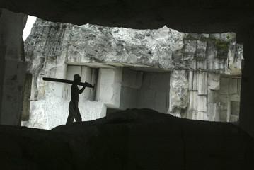 A brick maker carries his saw inside a limestone cave near Lamongan, East Java