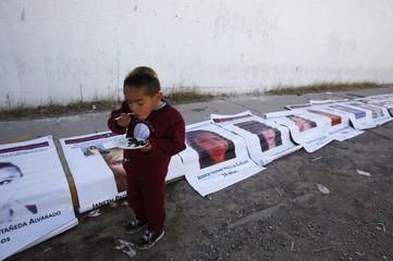 Boy eats birthday cake as he walks past photographs of missing women in Ciudad Juarez