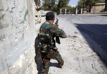 A Free Syrian Army fighter runs for cover during clashes in Aleppo