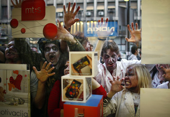 Actors dressed as zombies gesture as they look through the window display of a shop during a zombie walk in Belgrade