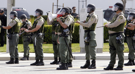 Riverside Sheriff Deputy Sergeant uses a bullhorn to get protesters to back down in their protest against a WalMart distribution center, which is closed today, in Mira Loma