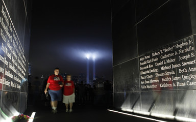 """People walk through the Empty Sky memorial as the """"Tribute in Lights"""" is illuminated over New York's Lower Manhattan skyline in Jersey City"""