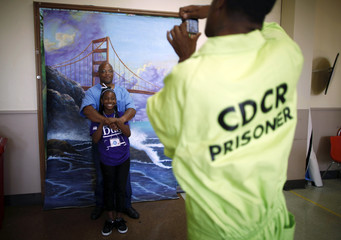 Troyanna hugs her father Troy, as they have picture taken in front of backdrop of Golden Gate Bridge after meeting for first time at San Quentin state prison