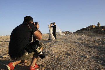 An Israeli couple poses for their wedding photographer as graves and a mosque are seen in the background in Judean desert near Jericho