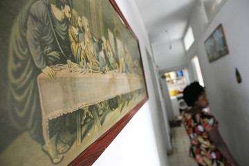 A foreign domestic worker walks past a picture of the Last Supper at a shelter run by Caritas in Dora