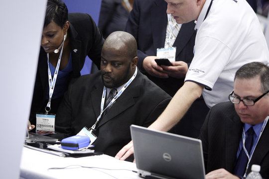 Corporate recruiters assist a jobseeker as he navigates an online application process on a laptop at the Hire Our Heroes job fair targeting unemployed military veterans and sponsored by the Cable Show, a cable television industry trade show in Washington