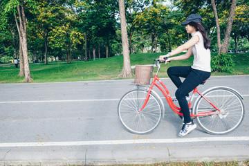 Healthy women with bike in green public park