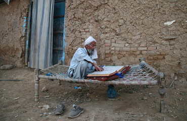 A man, who moved from a tribal area, reads the Koran while sitting on a rope bed in front of his mud house on the outskirts of Islamabad