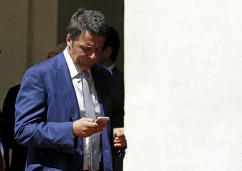 Italian PM Renzi checks phone before greeting Brazil President Rousseff at the Chigi palace in Rome