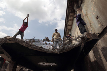 People remove scrap iron that will be sold to recycling companies from the ruins of a building damaged by a 1972 earthquake in the old centre of Managua