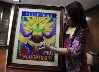 Ma. Josefina Dela Cruz, the Philippine postmaster general, gestures as she holds a copy of a Haiyan stamp inside the post office in Manila