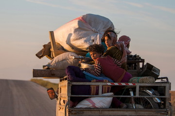 Residents return to their villages on a pickup truck after YPG fighters said that they retook control of the area from IS in the southern countryside of Ras al-Ain