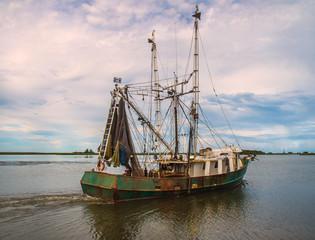 Shrimp trawler boat on water sailing on Florida coast